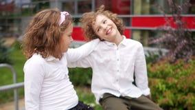 Σχολική φιλία Ένα ζευγάρι των εφήβων, ένα αγόρι και ένα κορίτσι κάθονται στο κιγκλίδωμα, το κορίτσι κρατά το χέρι της απόθεμα βίντεο