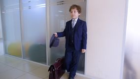 Σχολικό αγόρι στο επιχειρησιακό κοστούμι και καπέλο που στέκεται στο σχολικό διάδρομο πριν από την κατηγορία Σοβαρός επιχειρηματί απόθεμα βίντεο