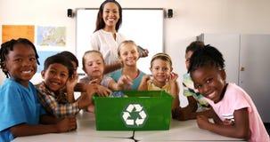 Σχολικά παιδιά που βάζουν τα μπουκάλια αποβλήτων στο ανακύκλωσης δοχείο στην τάξη απόθεμα βίντεο