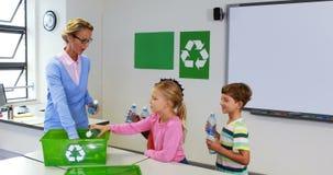 Σχολικά παιδιά που βάζουν το μπουκάλι στο ανακύκλωσης κιβώτιο λογότυπων στην τάξη απόθεμα βίντεο