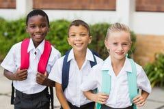 Σχολικά παιδιά που στέκονται στο σχολικό πεζούλι Στοκ Εικόνα