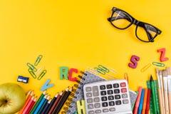 Σχολικά προμήθειες και eyeglasses στο κίτρινο υπόβαθρο Στοκ Εικόνες
