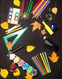 Σχολικές προμήθειες και φύλλα φθινοπώρου στο μαύρο υπόβαθρο Πίσω στο s Στοκ φωτογραφίες με δικαίωμα ελεύθερης χρήσης
