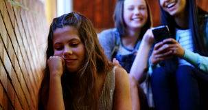 Σχολικοί φίλοι που φοβερίζουν ένα λυπημένο κορίτσι στο σχολικό διάδρομο φιλμ μικρού μήκους