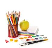Σχολικός εξοπλισμός με τα μολύβια, τα χρώματα, τις βούρτσες και το μήλο στο λευκό πίσω σχολείο έννοιας Στοκ Εικόνα