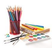 Σχολικός εξοπλισμός με τα μολύβια, το σημειωματάριο, τα χρώματα και τις βούρτσες στο λευκό πίσω σχολείο έννοιας Στοκ Εικόνες