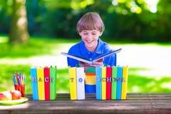 Σχολικό αγόρι που διαβάζει ένα βιβλίο Στοκ Εικόνες