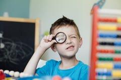 Σχολικό αγόρι που κοιτάζει μέσω μιας ενίσχυσης - γυαλί Στοκ φωτογραφίες με δικαίωμα ελεύθερης χρήσης