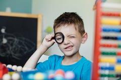 Σχολικό αγόρι που κοιτάζει μέσω μιας ενίσχυσης - γυαλί Στοκ Εικόνα