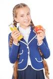 Σχολικό κορίτσι με το χυμό και το μήλο Στοκ Εικόνες