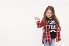 Σχολικό κορίτσι παιδιών που δείχνει με το δάχτυλο που απομονώνεται στο λευκό στοκ φωτογραφία