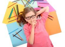 Σχολικό κορίτσι που βρίσκεται στο πάτωμα με τα μολύβια χρώματος Στοκ Φωτογραφία