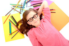Σχολικό κορίτσι που βρίσκεται στο πάτωμα με τα μολύβια χρώματος Στοκ Εικόνες