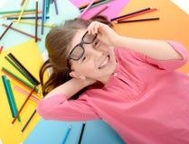 Σχολικό κορίτσι που βρίσκεται στο πάτωμα με τα μολύβια χρώματος Στοκ φωτογραφία με δικαίωμα ελεύθερης χρήσης