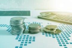 Σωροί και υπολογιστής νομισμάτων σε χαρτί της οικονομικής γραφικής παράστασης graphics Στοκ Εικόνα
