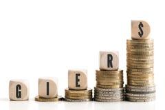 Σωροί νομισμάτων που συμβολίζουν την πλεονεξία με τη γερμανική λέξη για την πλεονεξία στους κύβους στοκ εικόνες με δικαίωμα ελεύθερης χρήσης