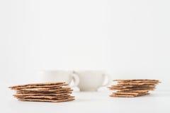 Σωροί των καφετιών σουηδικών κροτίδων ψωμιού σίκαλης τριζάτων με δύο φλυτζάνια στο άσπρο υπόβαθρο με το διάστημα για το κείμενο Στοκ εικόνες με δικαίωμα ελεύθερης χρήσης