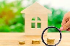 Σωροί των νομισμάτων και ενός ξύλινου σπιτιού Η έννοια των χρημάτων αποταμίευσης για την αγορά ενός σπιτιού Αγοράστε ένα διαμέρισ στοκ εικόνα