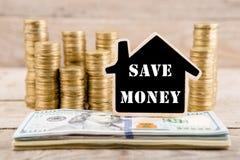 Σωροί των νομισμάτων και των λογαριασμών δολαρίων, πίνακας με μορφή ενός σπιτιού με το κείμενο & x22 SAVE MONEY& x22  στοκ εικόνες με δικαίωμα ελεύθερης χρήσης