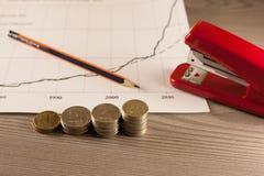 Σωροί των νομισμάτων χρημάτων με το έγγραφο και stapler γραφικών παραστάσεων Στοκ εικόνες με δικαίωμα ελεύθερης χρήσης
