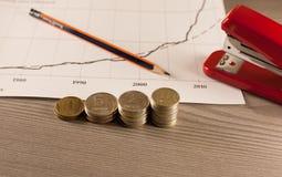 Σωροί των νομισμάτων χρημάτων με το έγγραφο και stapler γραφικών παραστάσεων Στοκ φωτογραφίες με δικαίωμα ελεύθερης χρήσης