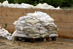 Σωρός άσπρα sandbags που χρησιμοποιούνται για την προστασία πλημμυρών που τίθεται στην ξύλινη αναμονή παλετών που αφαιρείται μετά στοκ εικόνες