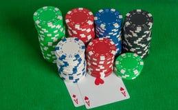 Σωρός άσσων ζευγαριού και τσιπ πόκερ στον πράσινο πίνακα Στοκ εικόνες με δικαίωμα ελεύθερης χρήσης