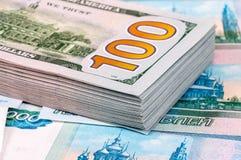 Σωρός εκατό αμερικανικών τραπεζογραμματίων δολαρίων πέρα από τα ρούβλια Στοκ εικόνες με δικαίωμα ελεύθερης χρήσης