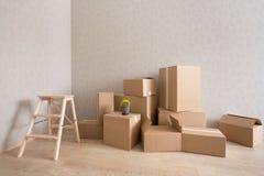 Σωρός κουτιών από χαρτόνι στο νέο κενό δωμάτιο με την βήμα-σκάλα στοκ εικόνες