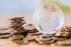 Σωρός νομισμάτων και σφαίρα γυαλιού Στοκ εικόνα με δικαίωμα ελεύθερης χρήσης