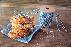Σωρός πύργων των μπισκότων με τους σπόρους σουσαμιού στην μπλε πετσέτα με μια μπλε κορδέλλα στο ξύλινο υπόβαθρο Υπόβαθρο μπισκότω Στοκ εικόνα με δικαίωμα ελεύθερης χρήσης