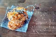 Σωρός πύργων των μπισκότων με τους σπόρους σουσαμιού στην μπλε πετσέτα με μια μπλε κορδέλλα στο ξύλινο υπόβαθρο Υπόβαθρο μπισκότω Στοκ Εικόνες