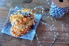 Σωρός πύργων των μπισκότων με τους σπόρους σουσαμιού στην μπλε πετσέτα με μια μπλε κορδέλλα στο ξύλινο υπόβαθρο Υπόβαθρο μπισκότω Στοκ Εικόνα