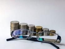 Σωρός στενού επάνω χρημάτων με τα γυαλιά στοκ φωτογραφία
