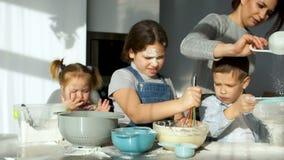 Σωρός στην κουζίνα Τρία εύθυμα παιδιά ζυμώνουν τη ζύμη για τις πίτες Το Mom τους βοηθά να κοσκινίσουν το αλεύρι Οικογενειακό μαγε απόθεμα βίντεο