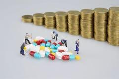 Σωρός της ιατρικής με τους μικροσκοπικούς ανθρώπους και τα νομίσματα θαμπάδων στοκ εικόνα με δικαίωμα ελεύθερης χρήσης