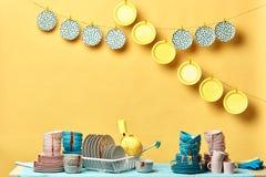 Σωρός του βρώμικου ζωηρόχρωμου σκεύους για την κουζίνα στο κίτρινο υπόβαθρο στοκ εικόνα με δικαίωμα ελεύθερης χρήσης