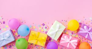 Σωρός του δώρου ή των παρόντων κιβωτίων, ζωηρόχρωμα μπαλόνια και κομφετί στη ρόδινη άποψη επιτραπέζιων κορυφών κρητιδογραφιών Υπό στοκ εικόνα
