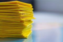 Σωρός του κίτρινου εγγράφου για τον μπλε πίνακα στοκ εικόνες