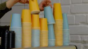 Σωρός του μίας χρήσης φλυτζανιού καφέ χρώματος Το ανθρώπινο χέρι παίρνει τα χρωματισμένα φλυτζάνια εγγράφου απόθεμα βίντεο