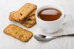 Σωρός του μπισκότο-muesli, φλυτζάνι του τσαγιού, κουταλάκι του γλυκού στον πίνακα Στοκ εικόνα με δικαίωμα ελεύθερης χρήσης