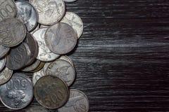 Σωρός του νομίσματος στο μαύρο ξύλινο σχέδιο Στοκ εικόνες με δικαίωμα ελεύθερης χρήσης