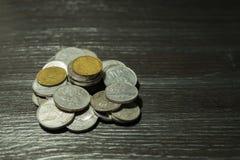 Σωρός του νομίσματος στο μαύρο ξύλινο σχέδιο Στοκ Εικόνα