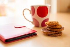 Σωρός του φλυτζανιού και της ταμπλέτας μπισκότων σε κόκκινη περίπτωση δέρματος στοκ φωτογραφία