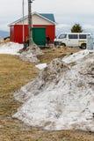 Σωρός του χιονιού στο καφετί έδαφος χλόης με το σπίτι, το φορτηγό και τους ανθρώπους στο υπόβαθρο το χειμώνα στο Hokkaido, Ιαπωνί Στοκ εικόνα με δικαίωμα ελεύθερης χρήσης