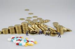 Σωρός του χρυσού νομίσματος με τους μικροσκοπικούς ανθρώπους και την ιατρική θαμπάδων στοκ φωτογραφία