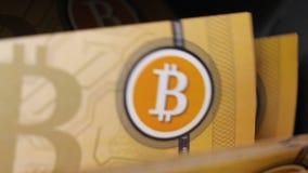 Σωρός τραπεζογραμματίων Bitcoin που μετριέται και που τίθεται με τη συσκευή φιλμ μικρού μήκους