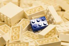 Σωρός των άσπρων δομικών μονάδων χρώματος με την εκλεκτικά εστίαση και το κυριώτερο σημείο σε έναν ιδιαίτερο μπλε φραγμό που χρησ Στοκ φωτογραφία με δικαίωμα ελεύθερης χρήσης