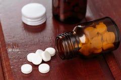 Σωρός των άσπρων χαπιών και των μπουκαλιών γυαλιού για τα φάρμακα σε ένα ξύλινο υπόβαθρο Στοκ Εικόνες