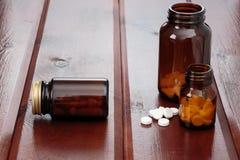 Σωρός των άσπρων χαπιών και των μπουκαλιών γυαλιού για τα φάρμακα σε ένα ξύλινο υπόβαθρο Στοκ Φωτογραφία